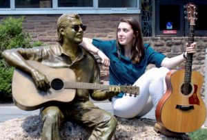 Emma Spies, the 2016 Danny DeGennaro Foundation scholarship winner, poses with a sculpture of Danny DeGennaro at Bucks County Community College.
